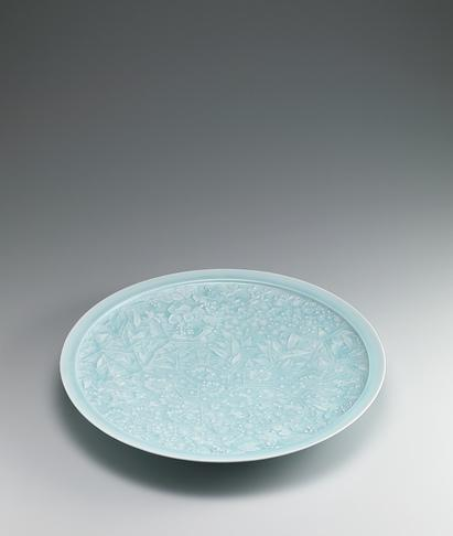 写真:Large white porcelain dish with pale blue glaze and flowering plant design.