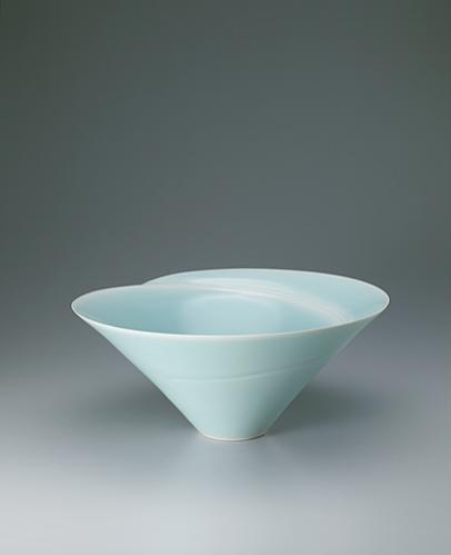 写真:Large white porcelain bowl with pale blue glaze and blurred white decoration.